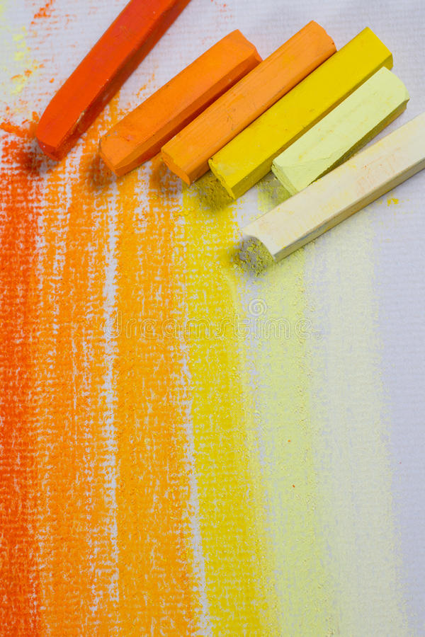 Yellow and orange pastels. Yellow and orange chalky soft pastels on textured paper. Copy space stock photos