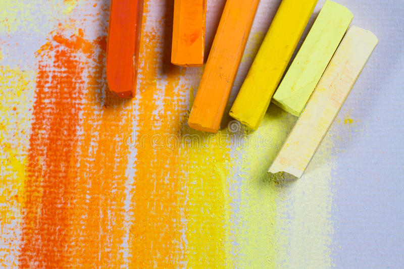 Yellow and orange pastels. Yellow and orange chalky soft pastels on textured paper. Copy space royalty free stock image