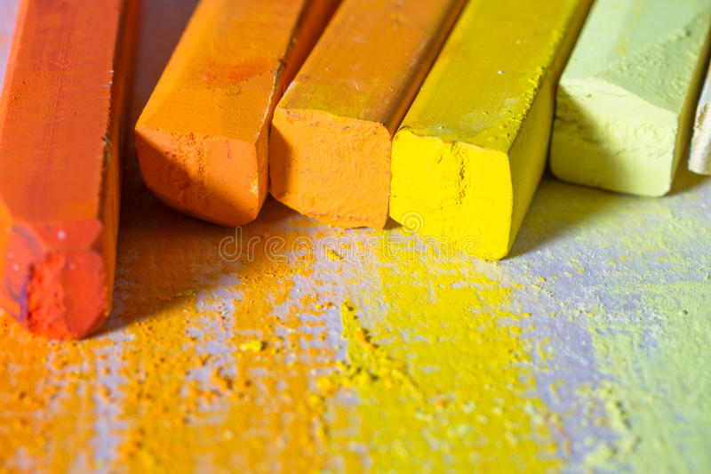 Yellow and orange pastels. Yellow and orange chalky soft pastels on textured paper. Copy space royalty free stock images