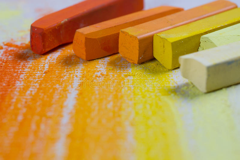 Yellow and orange pastels. Yellow and orange chalky soft pastels on textured paper. Copy space stock image