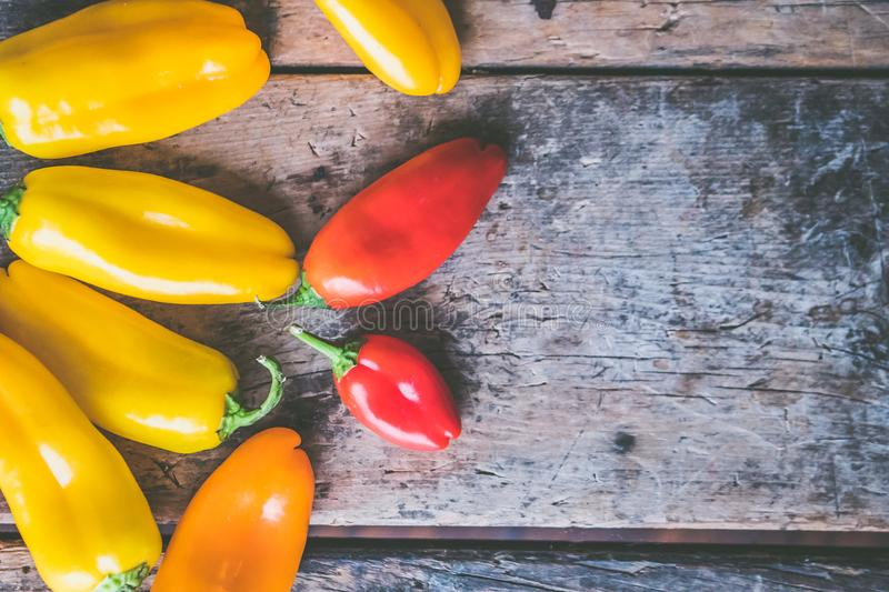 Yellow, Orange, and Red Peppers on Wooden Surface royalty free stock photography