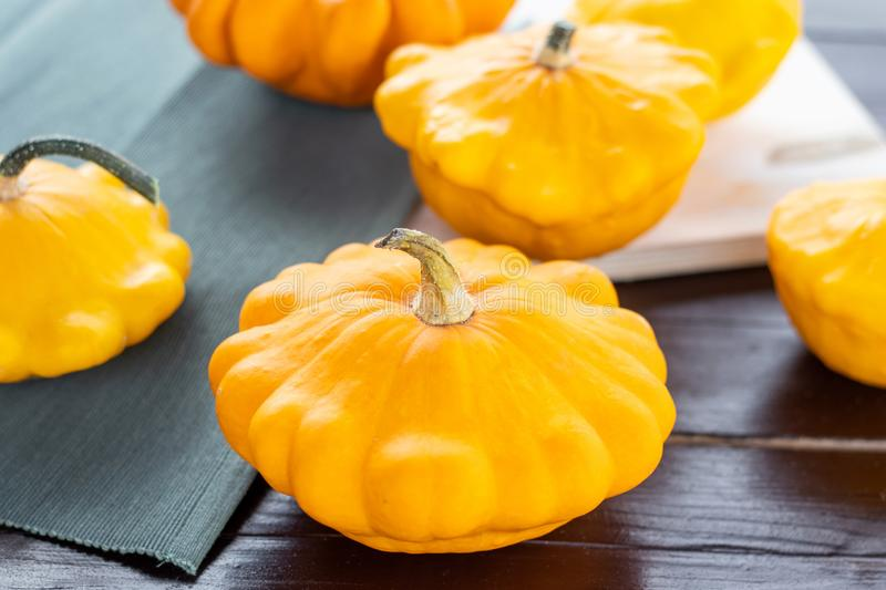 Yellow and orange summer squash, small pumpkins on a wooden table, autumn harvest, thanksgiving and farm food concept. Yellow and orange summer squash, fresh royalty free stock image