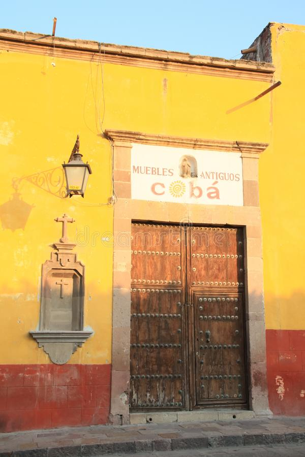 Yellow and Orange Wall and Wood Door at Sunset in a Mexico stock photography