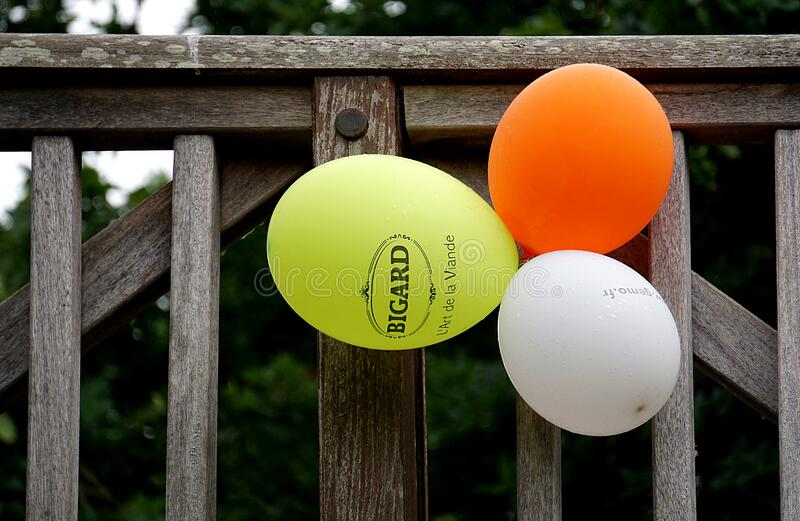 Yellow Orange and White Balloon Beside Gray Wooden Fence royalty free stock photo
