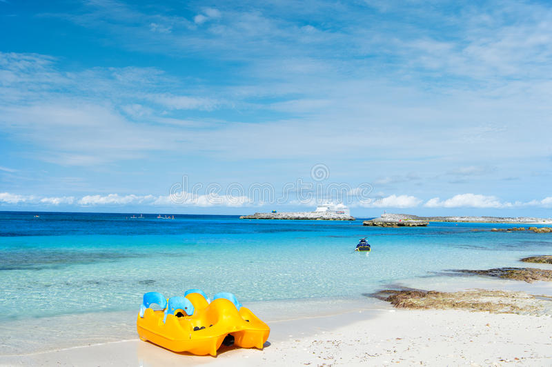 Yellow paddle boat. On white sand beach near sea or ocean water of tropical vacation resort on sunny summer day on blue sky stock image