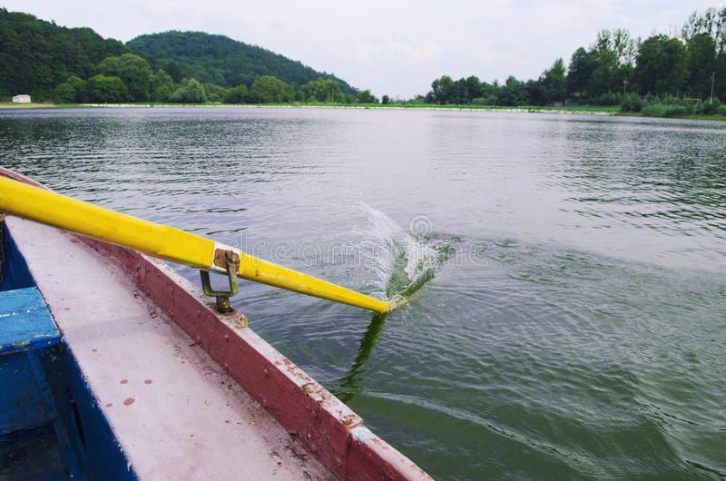 Yellow paddle in the water. Boating on river. Oar of boat touching water royalty free stock photo