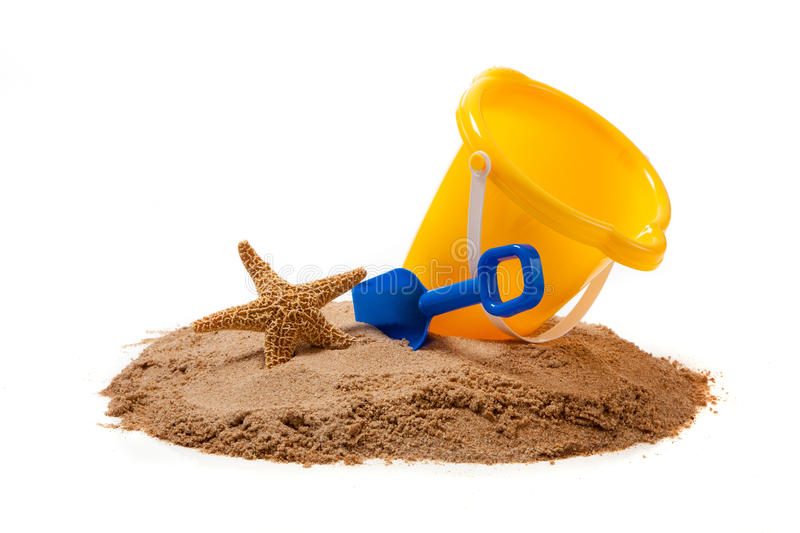 A yellow pail and blue shovel on the beach with a starfish. A yellow pail, blue shovel and a starfish on sand on a white background with copy space royalty free stock images