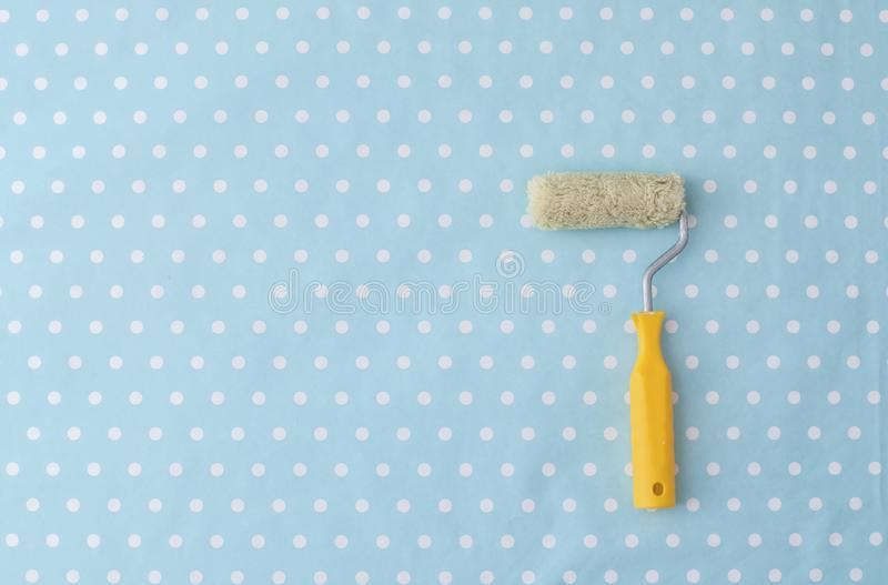 Yellow paint roller over blue polka dot wallpaper royalty free stock photography