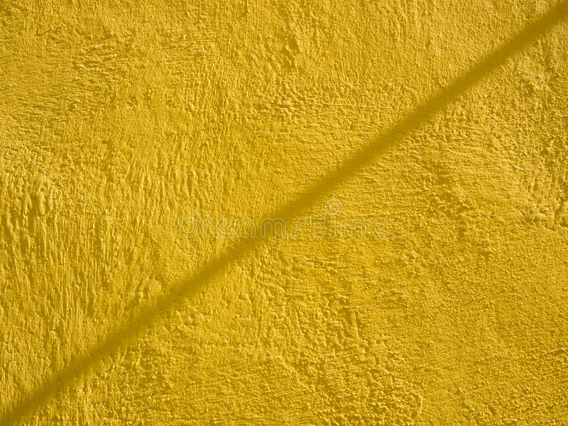 Yellow painted cement wall with line shadow. Abstract grunge texture background. Copy space, empty template for text royalty free stock images