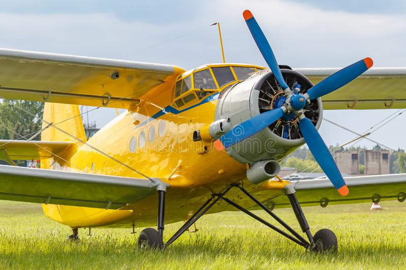 Yellow painted legendary soviet aircraft biplane Antonov AN-2 parked on a green grass of airfield closeup stock image