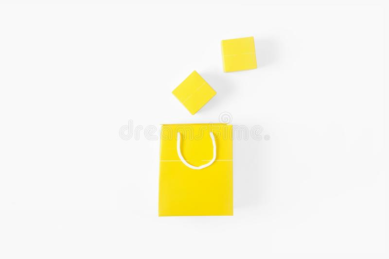 Yellow paper bag small yellow gift boxes white background top view flat lay stock image