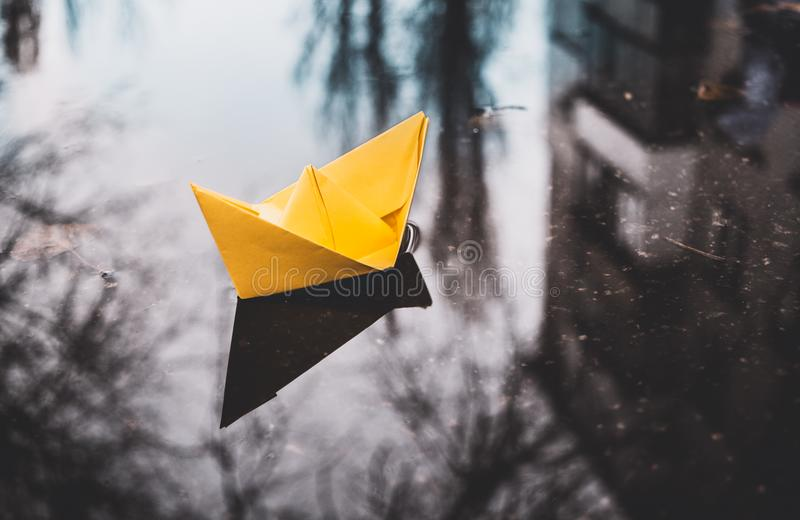 Yellow paper boat in a city street puddle. Autumn optimism. Bright yellow paper boat on a background of gloomy autumn urban puddles. Happiness and hope during stock photography