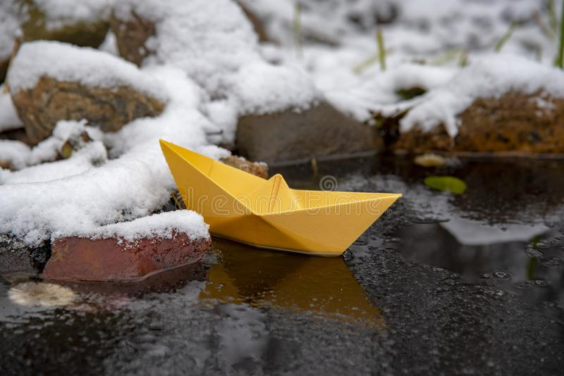 Yellow paper boat stuck in the ice, on a frozen puddle stock photo
