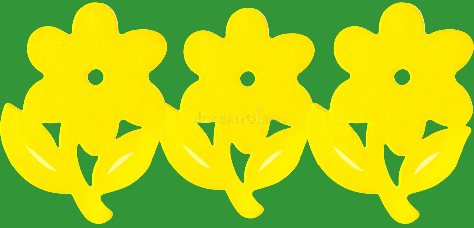 Yellow paper flowers. Border on a green background stock photo