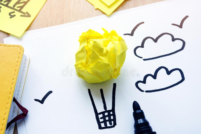 Yellow paper in form of air balloon as dreams. Procrastination or vacation. stock photography