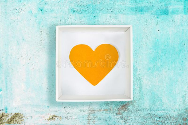 Yellow paper heart in white cardboard box on old turquoise metal background stock photography