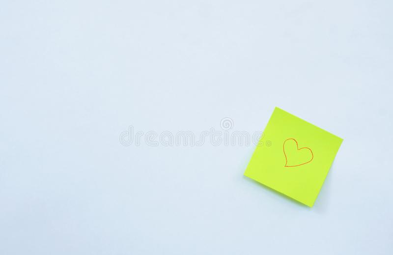 Yellow paper note drawing red heart shape stick on white background. Yellow paper note drawing red heart shape stick on the white background royalty free stock images