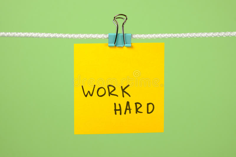 """Yellow paper note on the string with text """"Work Hard"""". Yellow paper note on the string with text Work Hard over colorful background royalty free stock photography"""