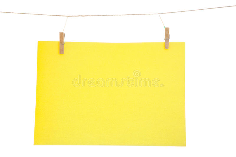Yellow paper sheet. Yellow blank paper sheet on a clothes line. Isolated on white background stock photography