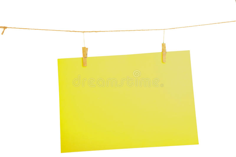 Yellow paper sheet. Yellow blank paper sheet on a clothes line. Isolated on white background royalty free stock image