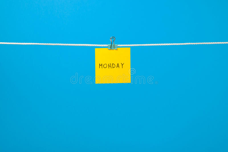 Yellow paper sheet on the string with text Monday stock photography