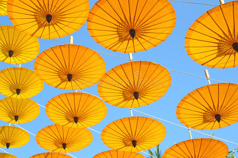 Yellow paper umbrella floating in the blue sky. stock photography