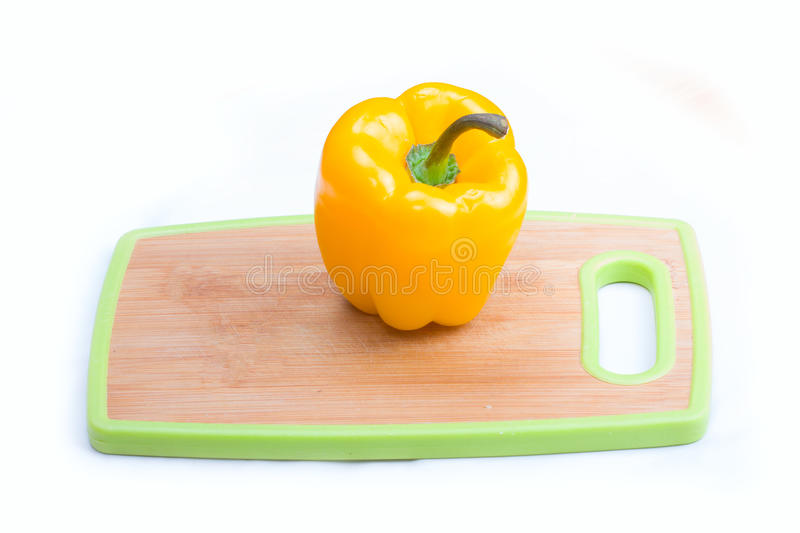 Yellow paprika on wooden board. Yellow paprika on a white background on board stock photos
