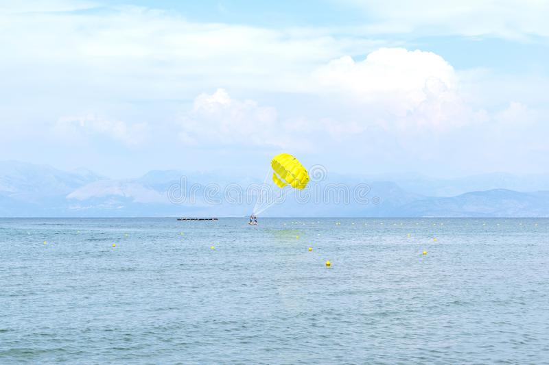 Yellow parachute in the blue sky over the sea on the island of Corfu, Greece. Parasailing extreme sports on the beach. stock photos