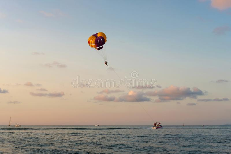 A yellow parachute by speed boat on sea. People flying with a yellow parachute by speed boat on sea royalty free stock photos