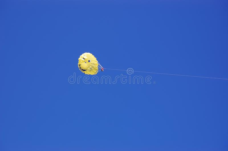Yellow parachute with a tourist in the background of a blue sky. A soaring yellow parachute with a tourist in the background of a bright blue sky royalty free stock photo