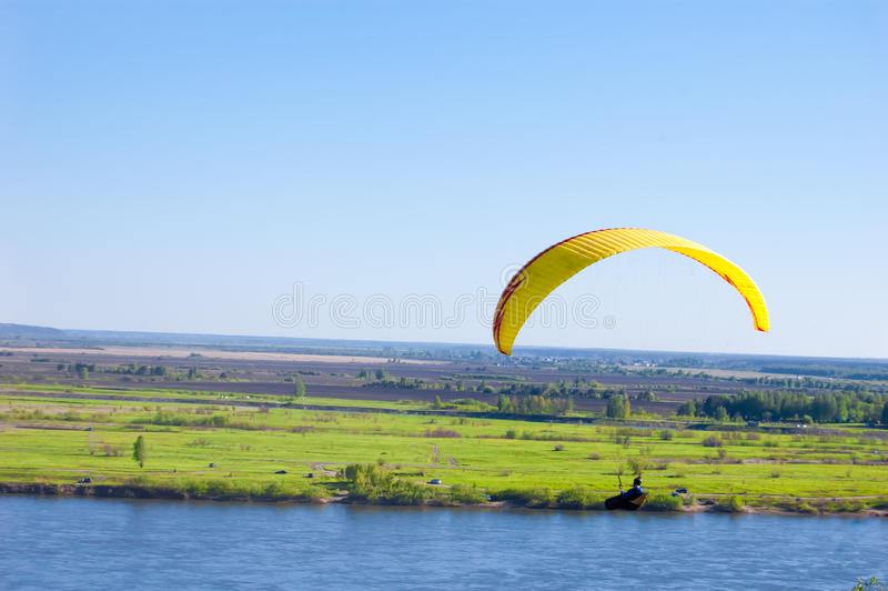 Yellow Paraglider in blue sky above the river and riverside. Bird`s eye panorama. Tom river. Tomsk city, Russia royalty free stock images