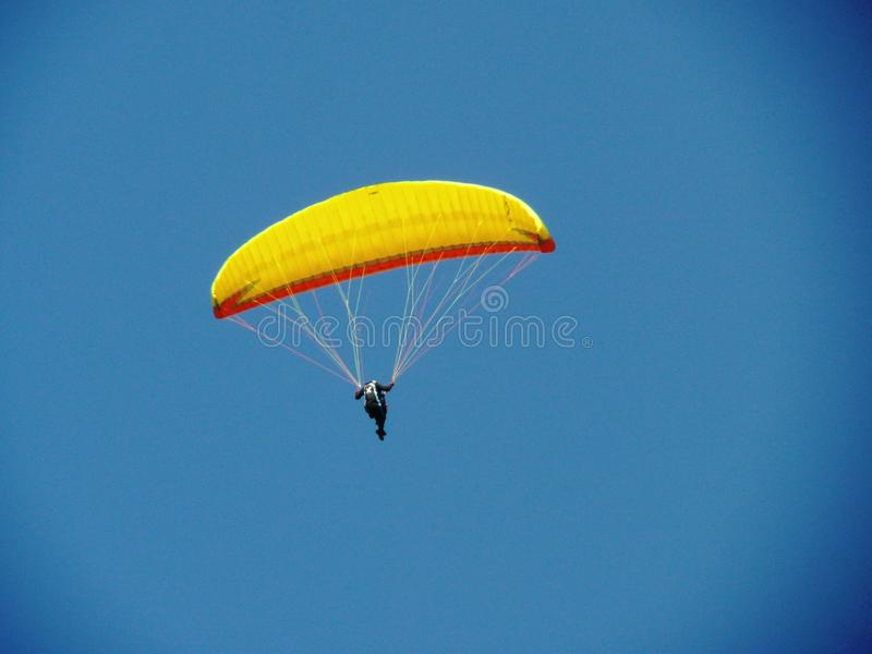 Yellow paraglider on blue sky. royalty free stock images