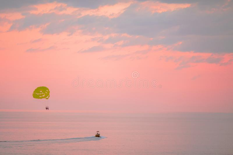 Yellow parasail wing pulled by a boat on beautiful pink sunset royalty free stock photography
