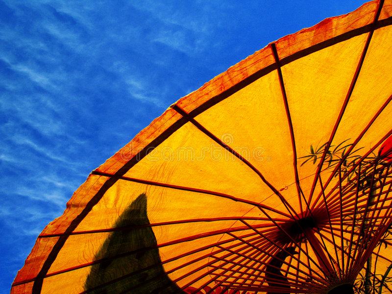 Yellow parasol and blue sky. Sweeping graphic element of yellow and orange parasol against blue sky. Suitable for illustrating travel and tourism concepts stock photography