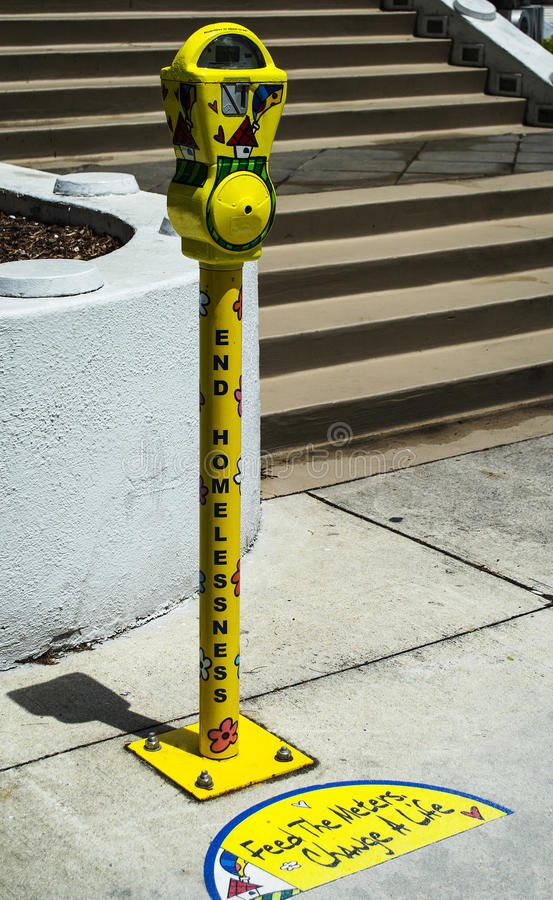 End homelessness. Yellow sculpture parking meter with the text saying end homelessness in downtown Miami royalty free stock images