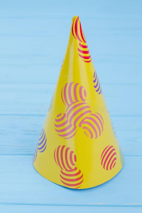 Yellow party hat on blue background. Kids Birthday cap on on color background, vertical image. Festive accessory for holiday party stock photo