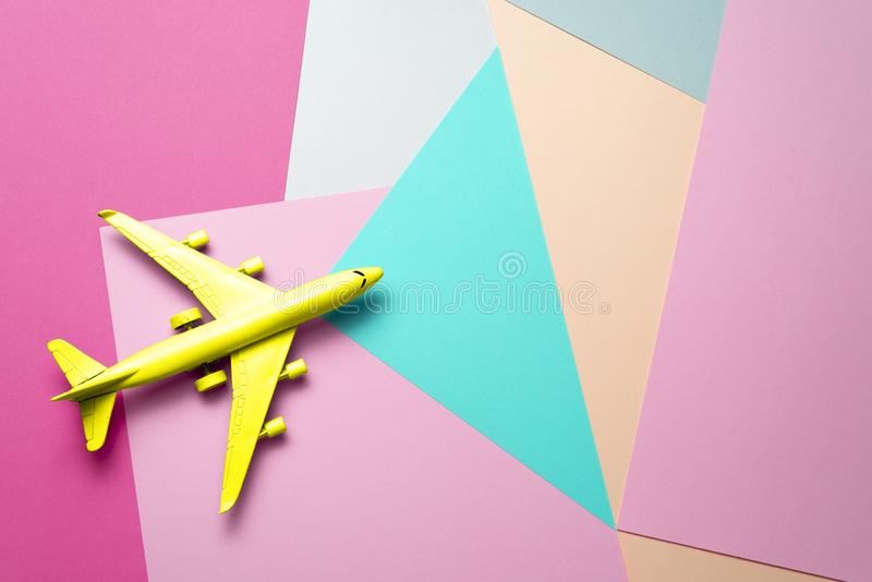 Yellow passenger jet airplane, travel minimal idea. multicolor paper funny background. Yellow passenger jet airplane, minimal concept, multicolor paper funny royalty free stock image