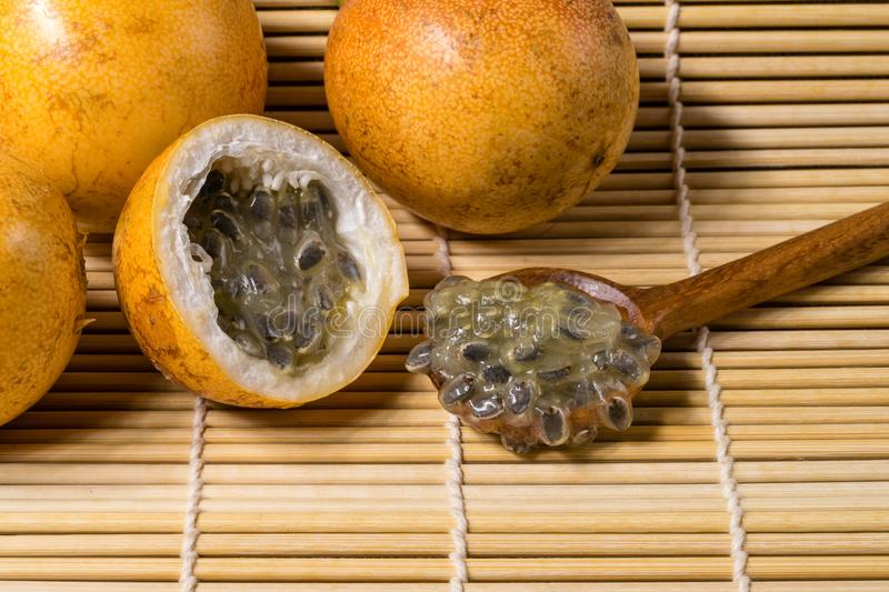 Yellow passion fruit or passiflora flavicarpa. Fresh and ripe yellow passion fruit on wooden table mat and wooden spoon stock photography