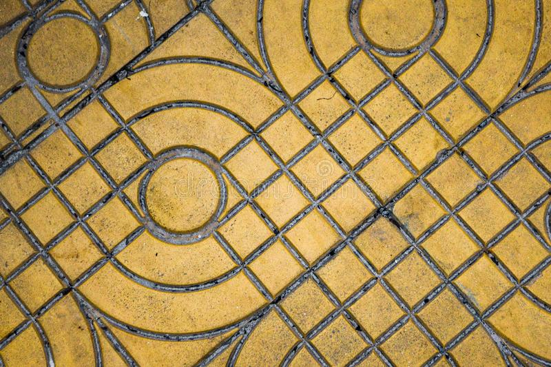 Yellow patterned paving tiles on the street, top view. Cement bricks, squared stone ground floor background texture royalty free stock photography