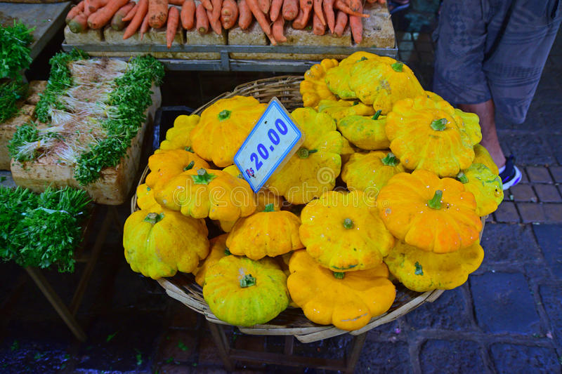 Yellow Pattypan squash sold at old market, Port Louis, Mauritius. Yellow brightly coloured Pattypan squash, resembling flying saucer, sold in basket at old stock photo