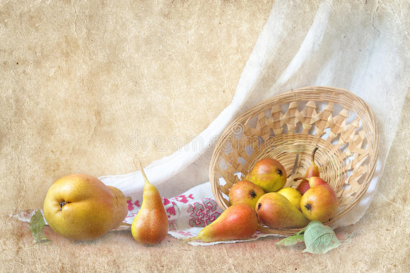 Yellow pear with red barrels on a straw plate with a white linen stock photography
