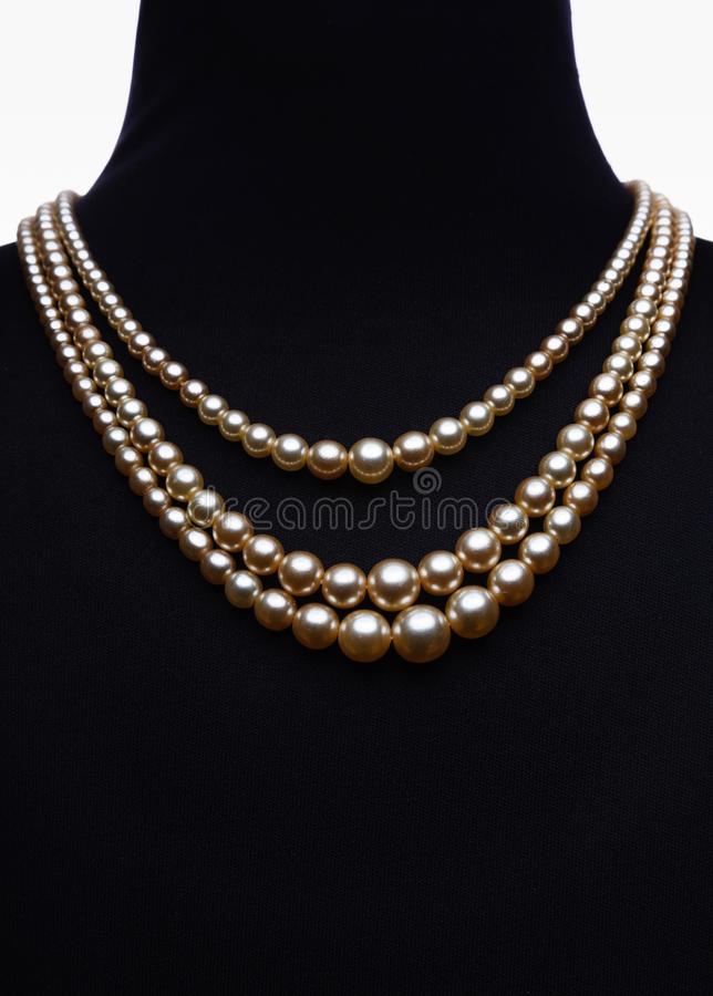 Yellow pearl necklace on black mannequin isolated royalty free stock photography