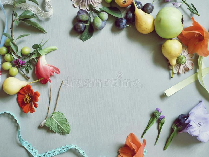 Yellow pears, apples, plums, fresh flowers, leaves, seasonal composition on a light background royalty free stock photo
