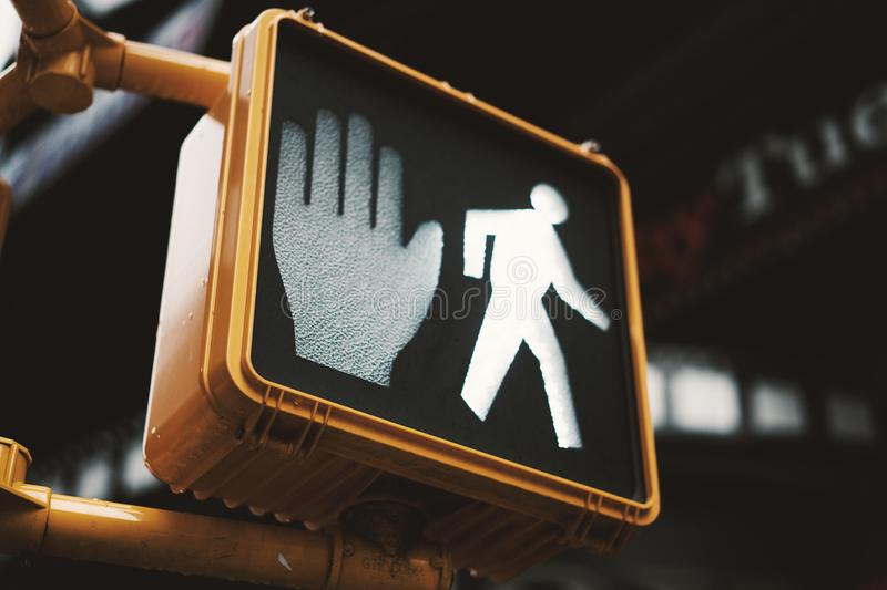 Yellow pedestrian crossing sign with walk light on in New York, Manhattan. royalty free stock images