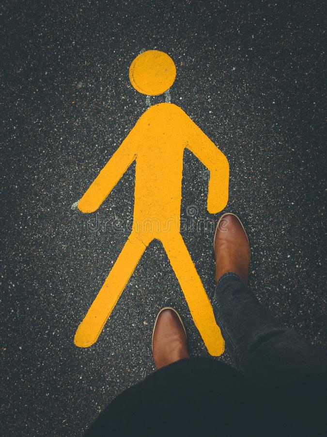 yellow pedestrian sign on street pavement with feet royalty free stock images