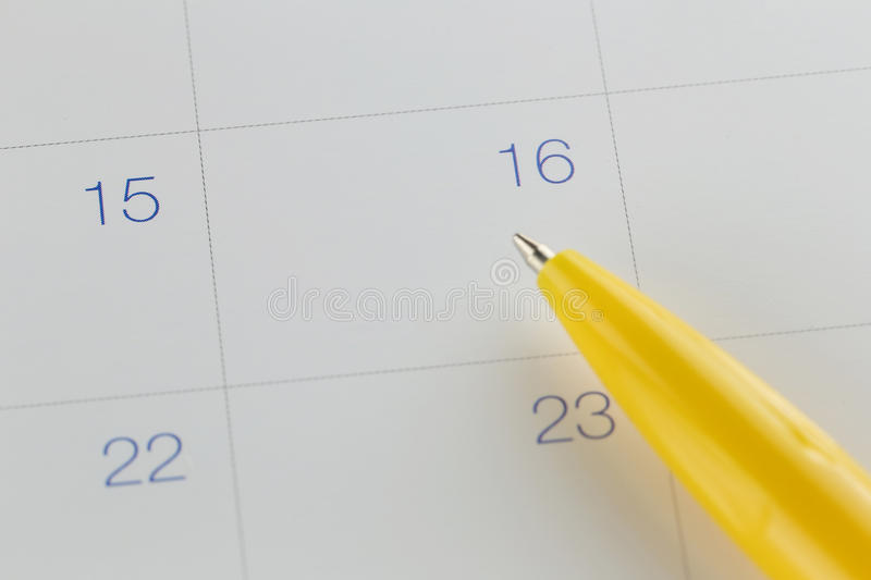 Yellow pen points to the number 16 on calendar background. Yellow pen points to the number 16 on calendar background in concept of appointment schedules and royalty free stock images