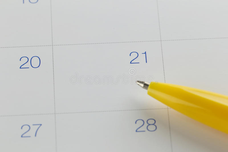 yellow pen points to the number 21 on calendar background. stock photos