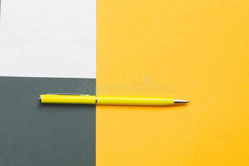 Yellow pen and note on colored background. Yellow pen and white note on colored background royalty free stock image