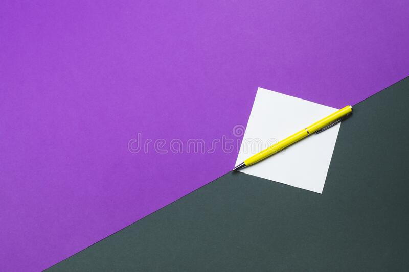 Yellow pen and note on colored background. Yellow pen and white note on colored background royalty free stock images