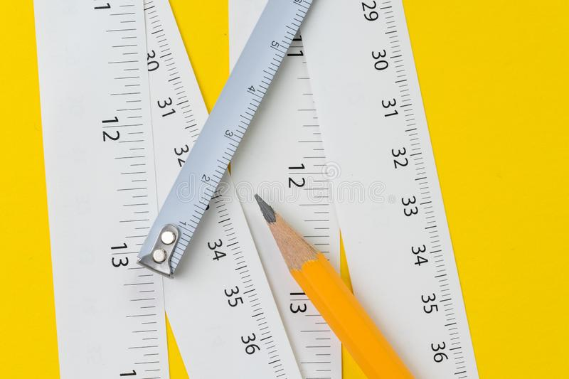 Yellow pencil and white measuring tapes with centimetre and inches on vivid yellow background, length, long or maker instrument royalty free stock photos